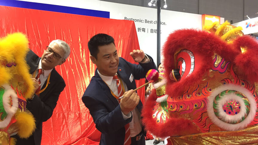 Jean-Pierre Neuhaus, Head of Corporate Communications, and You Song, President of Bystronic Group China, paint the eyes of the lion and the tiger. This is an ancient Chinese tradition. For good luck, a lion dance is a must at every major event. The veiled Xpress can be seen in the background.